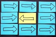 Pijlen op blauwe pagina's en gele met tegenovergestelde richting Individualiteit en uniciteit royalty-vrije stock afbeelding