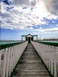 Pijler bij het strand tegen zeegezicht en bewolkte hemel stock foto's
