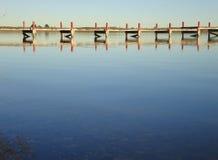 Pijler die bij kalm meer wordt weerspiegeld Stock Afbeeldingen