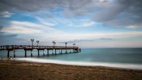 Pijler op het strand bij zonsondergang royalty-vrije stock foto
