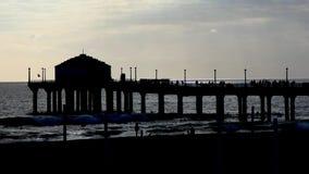 Pijler op kust op een strandrecht vóór zonsondergang stock footage