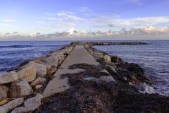 Pijler/pier van rotsen in zeewier en mooie hemel, cala bona, Mallorca, Spanje worden behandeld dat royalty-vrije stock afbeeldingen