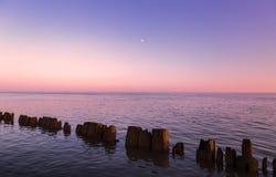 Pijlers in water bij zonsondergang Stock Fotografie