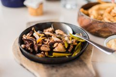 Pijlinktvis, groene paprika & uien op een sissende plaat wordt gediend die Stock Foto's