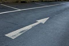 Pijlteken op asfaltoppervlakte Stock Foto