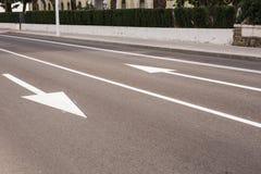 Pijltekens als wegnoteringen op een straat met twee stegen stock foto