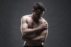 Pijn in de Schouder Spier mannelijk lichaam Het knappe bodybuilder stellen op grijze achtergrond Rustig dicht omhooggaand studios stock afbeelding