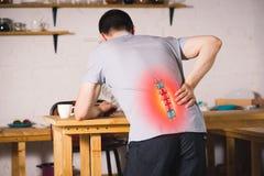 Pijn in de stekel, een mens met rugpijn thuis, verwonding in de lagere rug stock foto