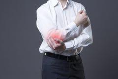 Pijn in elleboog, gezamenlijke ontsteking met rode punt op grijze achtergrond stock foto