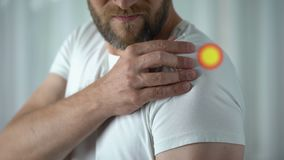 Pijn in schouder met vlek, mens wordt vermeld verwonde verbinding na lichaamsbeweging die stock footage