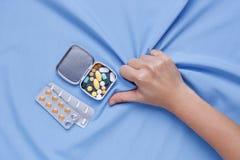 Pijn van de hand van de ziekteclose-up met pillen stock foto's