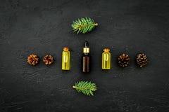 Pijnboometherische olie in flessen op de donkere ruimte van het achtergrond hoogste meningsexemplaar Patroon met pijnboomtak en k Royalty-vrije Stock Foto's
