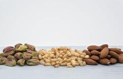 Pijnboomnoten, amandelen en pistaches op het hout Stock Afbeeldingen