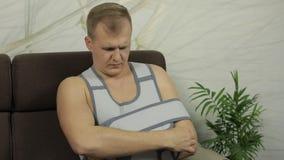 Pijnlijke, bored mens met een gebroken wapen die de zitting van de wapensteun op een bank dragen stock videobeelden