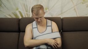 Pijnlijke, bored mens met een gebroken wapen die de zitting van de wapensteun op een bank dragen stock footage