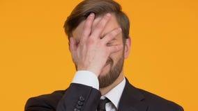 Pijnlijke mens die facepalm, geschokt met zijn fout, verliezer, close-up maken stock footage