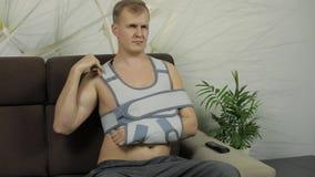 Pijnlijke mens met een gebroken wapen die de zitting van de wapensteun op een bank dragen die op TV letten stock footage