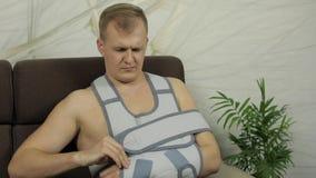 Pijnlijke mens met een gebroken wapen die de zitting van de wapensteun op een bank dragen die op TV letten stock video
