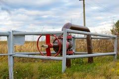 Pijp en een rode kleppijp dichtbij de hefbomen van de oliepomp royalty-vrije stock fotografie