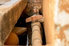 Pijp van close-up de Uitstekende Oude pvc met Rode Klep op Vuile Concrete Muur - Watervoorziening stock fotografie