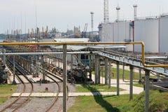 Pijpen en tanks in oliehaven Stock Afbeeldingen