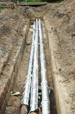 Pijpisolatie Het systeem van de doorbraakriolering Pijpen voor water in een aarden geul stock afbeelding