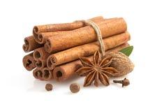 Pijpjes kaneel, anijsplantster en kruiden op wit Stock Foto's