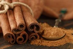 Pijpjes kaneel en poeder op rustieke houten Raad Stock Afbeeldingen