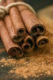 Pijpjes kaneel en poeder op rustieke houten Raad Stock Fotografie
