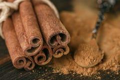 Pijpjes kaneel en poeder op rustieke houten Raad Stock Afbeelding