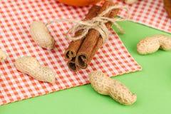 Pijpjes kaneel en ruwe pinda's op een heldere achtergrond stock foto's