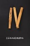 Pijpjes kaneel met hand van letters voorziende die teksten op een bord worden geschreven Royalty-vrije Stock Foto's