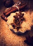 Pijpjes kaneel, noten en steranijsplant op bruine suiker, macro. Baki Stock Foto's