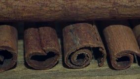 Pijpjes kaneel op een houten lijst Dichtbij een koffiemolen en verpakkende documenten 4K stock footage