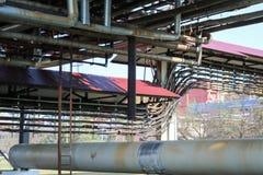 Pijpleidingsviaduct met ijzer roestige pijpen voor het pompen van vloeistof, gecondenseerd met afzet en afvoerkanalen in olieraff royalty-vrije stock fotografie
