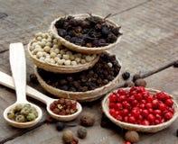 pikantność Czarny pieprz, biel, menchia, zieleń, cubeb na drewnianym tle Fotografia Royalty Free