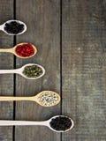 pikantność Czarny pieprz, biel, menchia, zieleń, cubeb w drewnianych łyżkach na drewnianym tle Obraz Stock