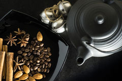 Pikantność kawowe fasole z teapot i dzwonami na czarnym tle fotografia stock