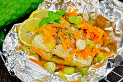 Pike with carrots and basil in foil on board Royalty Free Stock Image