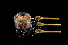 Pike caviar, roe in a glass jar, wooden spoons with spices for fish, sea salt on a black background, close-up, set royalty free stock photography