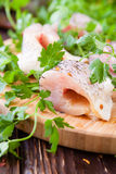 Pike fillet pieces on a cutting board and a sprig of parsley Royalty Free Stock Photos