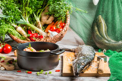 Pike and fresh vegetables for fish soup. On old wooden table Royalty Free Stock Images