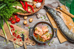 Pike and fresh vegetables for fish  soup. On old wooden table Royalty Free Stock Photo