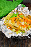Pike with leeks and carrots in foil on board royalty free stock image