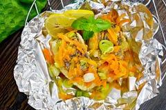 Pike mit Karotten und Basilikum in der Folie an Bord der Spitze lizenzfreies stockbild