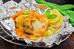 Pike mit Karotten und Zitrone in der Folie an Bord Stockbild