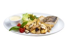 Pike perch with porcini mushrooms and potatoes. On a white plate royalty free stock photo