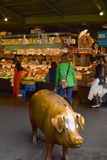 Pike Place Fish Market, Seattle, WA, USA. Visitors at iconic Seattle Pike Place Fish Market at the Public Market. Copper pig in foreground Royalty Free Stock Photos