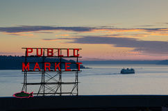 Pike Place Market Sign and Ferry at Sunset in Seattle. The Pike Place Market neon sign in Seattle at sunset with a Washington State Ferry crossing Elliott Bay Stock Photography