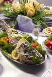 Pike prepared fish and some salads behaind Stock Photo